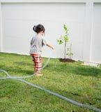 帮助她的父母的孩子浇灌植物 免版税库存图片