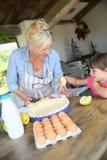 帮助她的祖母的小女孩做苹果饼 免版税库存图片