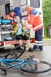帮助妇女自行车事故的紧急医务人员 库存图片