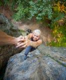 帮助对女性登山人的Rockclimber到达山上面  免版税库存图片