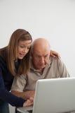 帮助对她的有计算机的祖父的女孩 免版税库存图片