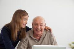 帮助对她的有计算机的祖父的女孩 免版税图库摄影