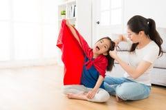 帮助小女孩疲乏的头发的微笑的母亲 免版税库存照片