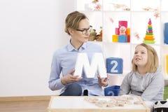 帮助小女孩的语言矫治者 免版税库存照片