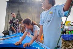 帮助小船的亚裔女孩用在古老老vihara大厅寺庙的手((水下的寺庙) 库存图片