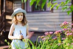 帮助小花匠儿童的女孩整理和被切开的spirea灌木在夏天庭院里 图库摄影