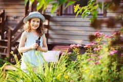 帮助小花匠儿童的女孩整理和被切开的spirea灌木在夏天庭院里 库存照片