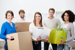 帮助小组不同种族的朋友移动房子 免版税库存照片