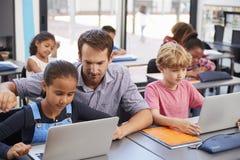 帮助年轻学生的老师使用膝上型计算机在类 免版税库存图片