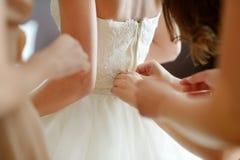 帮助新娘投入她的婚礼礼服 免版税图库摄影