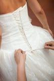 帮助新娘的女傧相投入她的礼服 免版税库存照片