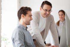 帮助有个人计算机的微笑的辅导者年轻专家工作 免版税库存照片