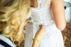 帮助有婚礼礼服的女傧相新娘 免版税库存照片