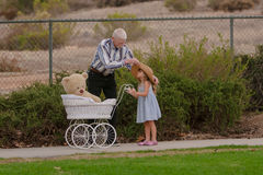帮助有帽子的祖父小女孩在与玩具儿童车的步行 免版税库存图片