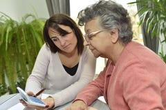 帮助有文书工作的家庭护工老人 库存照片
