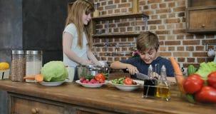 帮助有烹调的孩子切口菜,一起准备食物的愉快的家庭父母在厨房里 影视素材