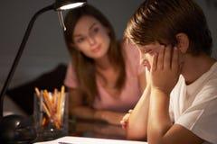 帮助有研究的少年姐妹被注重的弟弟在书桌在卧室在晚上 免版税图库摄影