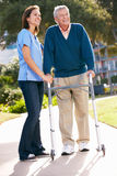 帮助有走的框架的护工老人 免版税库存图片