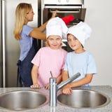 帮助母亲的孩子在厨房里 图库摄影