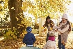 帮助母亲的孩子收集秋叶在庭院里 免版税库存照片