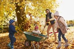 帮助父亲的孩子收集秋叶在庭院里 库存照片