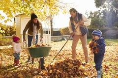 帮助父母的孩子收集秋叶在庭院里 免版税库存图片