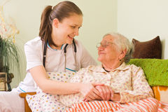 帮助病的妇女的年长的人 免版税库存照片