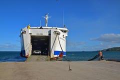 帮助的地勤人员通过拉扯&栓绳索靠码头大轮渡在登陆附近的苏瓦,斐济的Natovi 免版税库存照片