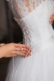 帮助的女傧相栓她的婚礼礼服 传统,新娘早晨 免版税库存图片