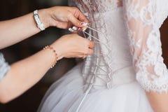 帮助的女傧相栓她的婚礼礼服 传统,新娘早晨 免版税图库摄影
