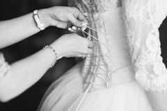 帮助的女傧相栓她的婚礼礼服 传统,新娘早晨 免版税库存照片
