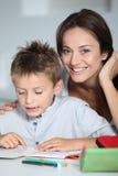 帮助的母亲读取儿子 免版税库存图片