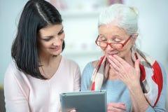 帮助的老妇人用途片剂计算机 免版税库存图片