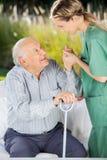 帮助老人的女性看守者起来从 库存图片