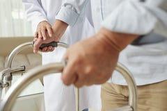 帮助老人的护士在医院 免版税库存图片