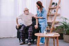 帮助老人的护士 免版税库存图片