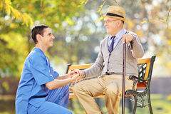 帮助老人的医疗保健专家坐长凳 库存图片
