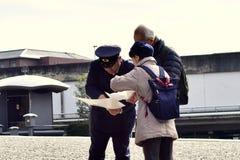 帮助老夫妇的日本警察 免版税图库摄影