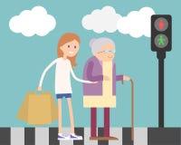 帮助老妇人的女孩 免版税库存照片