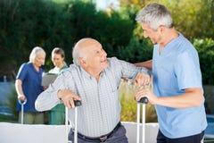 帮助老年人的男性和女性看守者 免版税库存图片