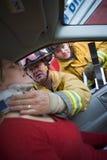 帮助被伤害的妇女的汽车消防队员 免版税图库摄影