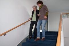 帮助资深妇女的照料者步行沿着向下台阶 库存照片