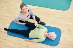 帮助资深妇女的理疗师做腿舒展 免版税库存照片