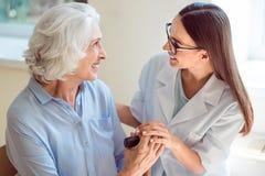 帮助资深患者的年轻人护士 免版税库存照片