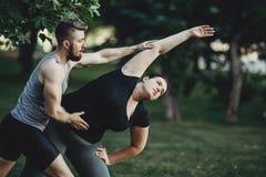 帮助超重妇女的个人教练员在街道锻炼 肥胖 图库摄影