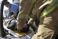 帮助车祸受害者的消防队员和医务人员 图库摄影