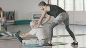 帮助退休的人的体育教练做在健身房锻炼的舒展锻炼 股票录像