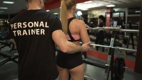 帮助适合的年轻女性的个人教练员举卷毛酒吧,作指示 股票录像