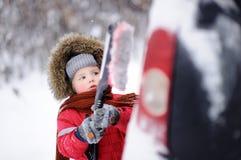 帮助逗人喜爱的小孩掠过从汽车的雪 免版税库存照片