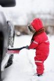 帮助逗人喜爱的小孩掠过从汽车的雪 库存照片